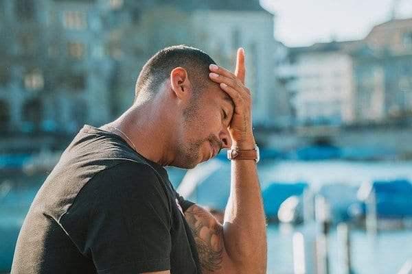 Mężczyzna trzyma się za głowę z powodu migreny i częstego bólu głowy