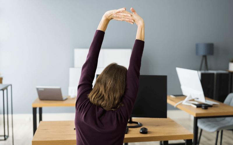 Kobieta ćwiczy przy biurku.